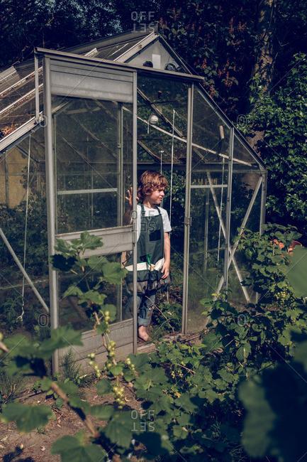 Kid posing on door in greenhouse