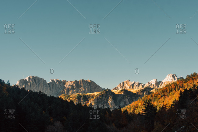 Landscape view with picturesque mountains covered with forest in sunny day.