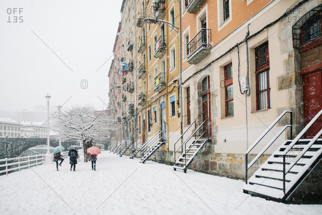 Unrecognizable people walking on snowy town