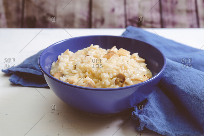 Appetizing risotto served in blue deep dish surrounded blue silk