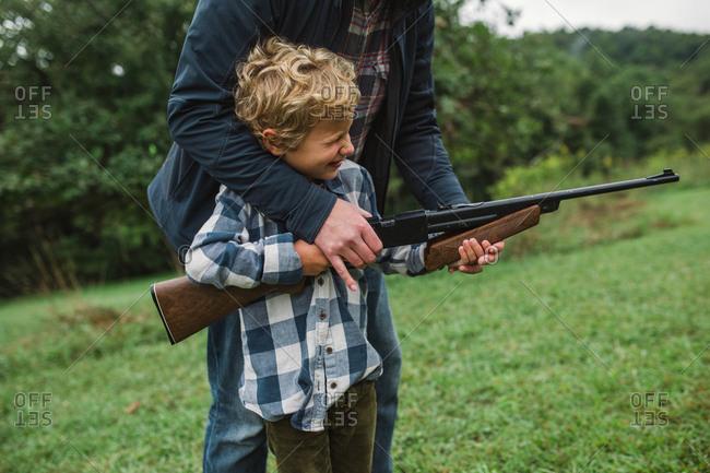 Father showing boy how to shoot a gun