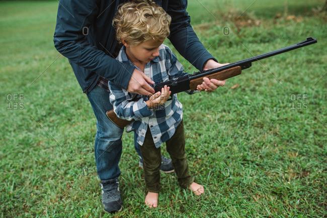 Father showing little boy how to shoot a gun