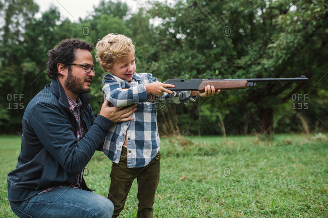 Father showing son how to shoot a gun