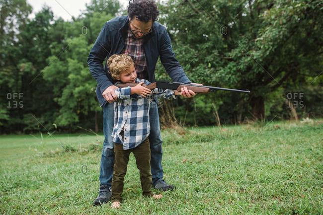 Father teaching son how to shoot a gun
