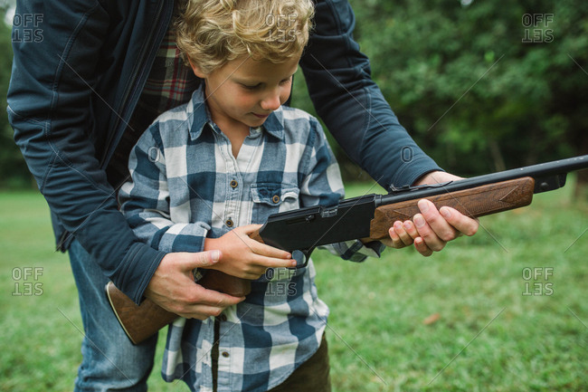 Father showing his son how to shoot a gun