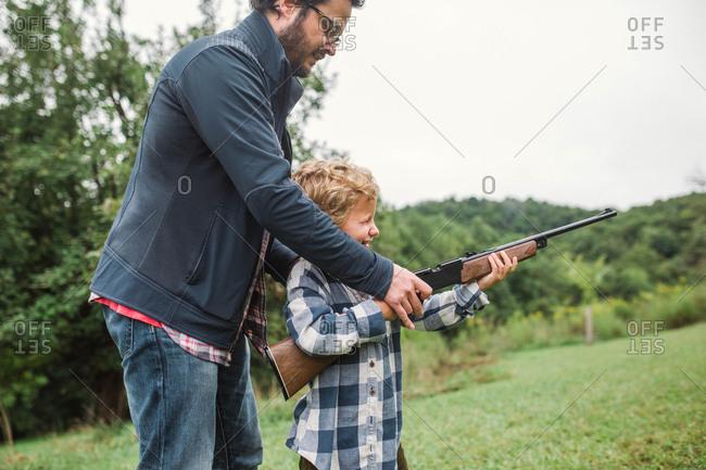 Father teaching boy how to shoot a gun
