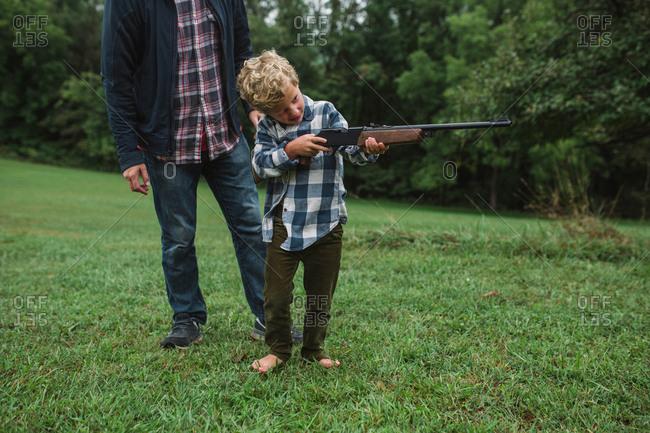 Man teaching boy how to shoot a gun