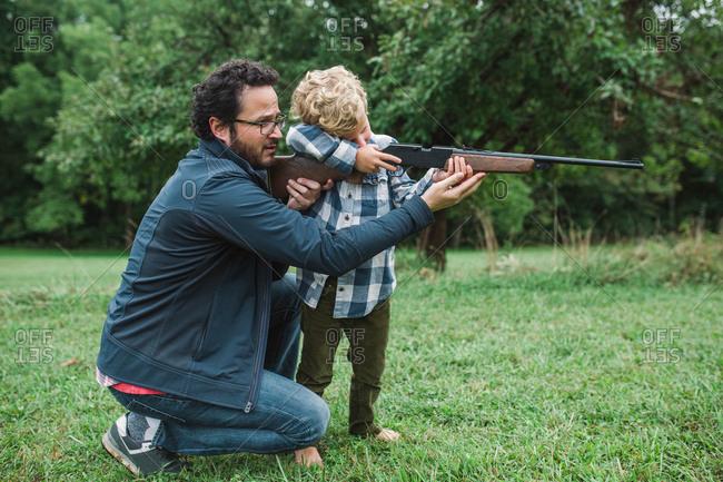 Man showing boy how to shoot a gun