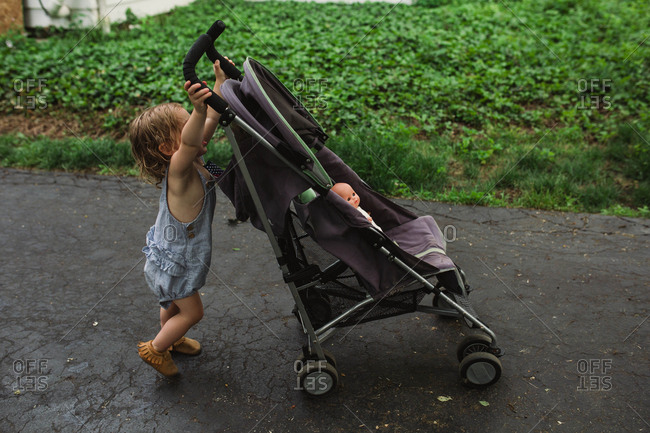 Baby pushing stroller with doll