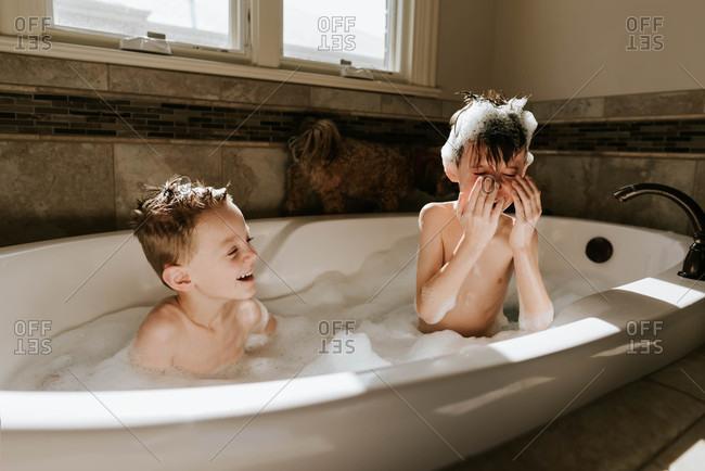 Two boys bathing in bubble bath