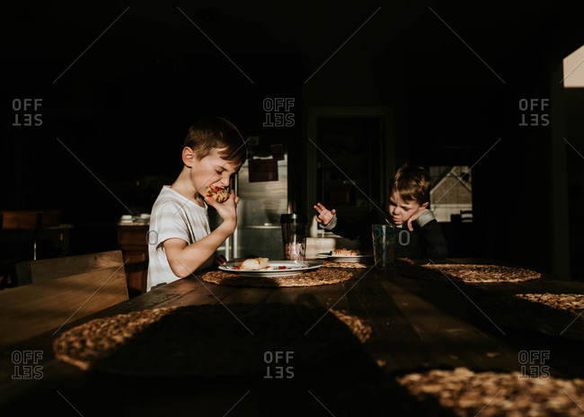 Two boys eating pizza for dinner at the kitchen table