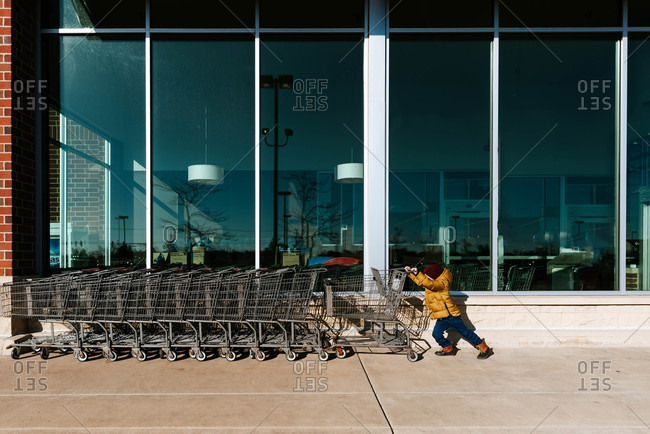 Boy putting cart back outside of grocery store