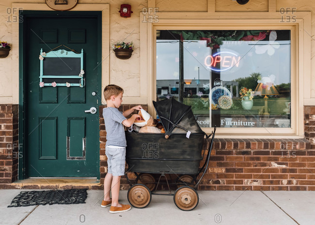 Young boy looking at toys outside an antique store