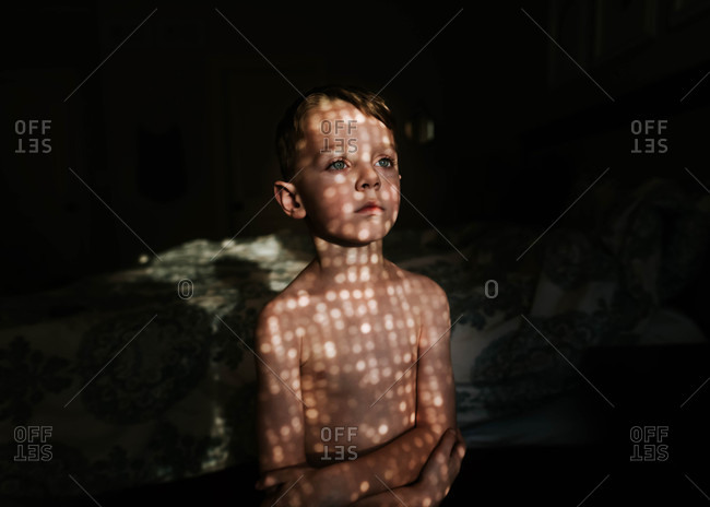 Portrait of a young boy standing in front of window with sunlight on his face