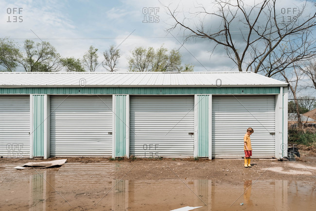 Boy standing by shed and large puddle looking away