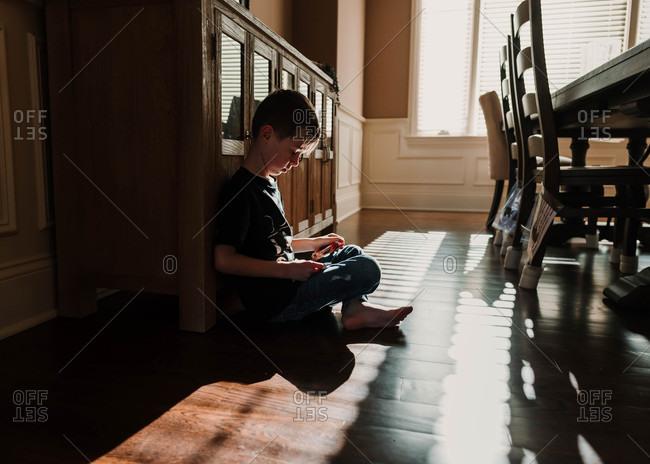 Boy sitting on floor in dining room