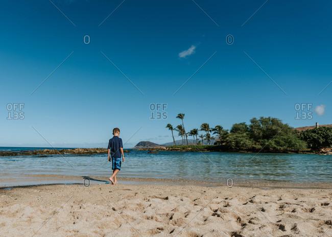 Young boy walking on beach in Hawaii
