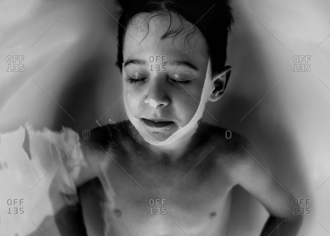 Overhead view of boy in bathwater in black and white