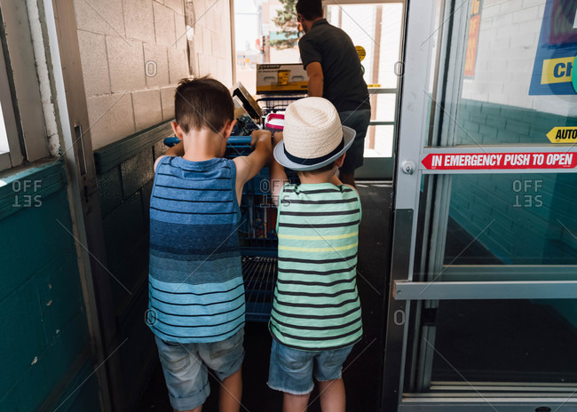 Boys pushing cart full of toys out store door