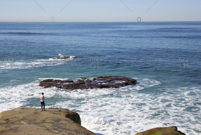 Woman on rocky beach in San Diego, California