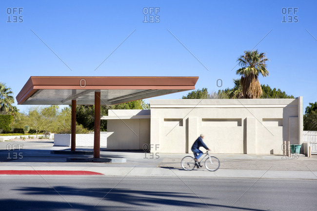Man riding bike by abandoned gas station, Palm Springs, California