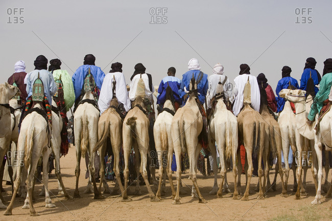 In-Gall, Niger - September 14, 2006: Rear view of Wodaabe tribe men on camels at the Cure Salee festival