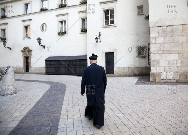Krakow, Poland - May 26, 2011: Catholic priest walking in courtyard