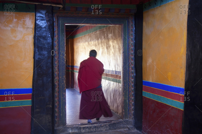 Buddhist monk in doorway at Lhasa Jokhang Palace, Tibet, China