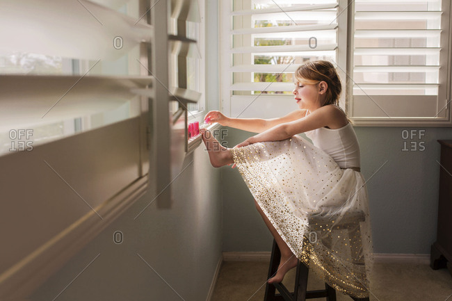 Little girl painting her toes near a window