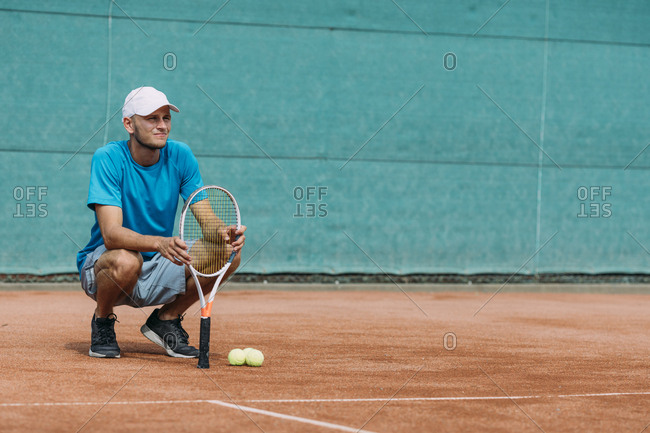Young man holding tennis racket on court