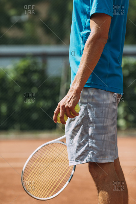 Man holding tennis balls and racket