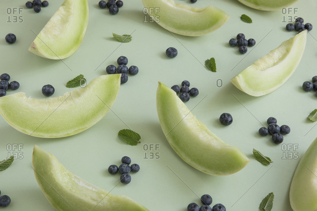 Slices of honeydew melon arranged with blueberries and mint leaves