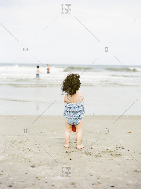 Back view of little girl standing on a sandy beach