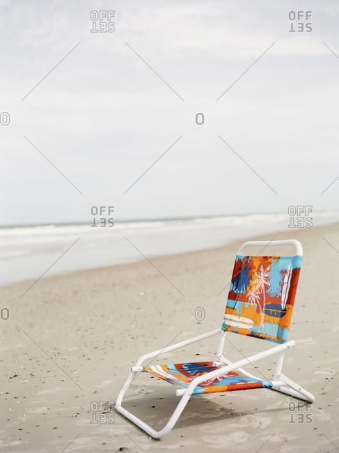 Empty chair on sandy beach
