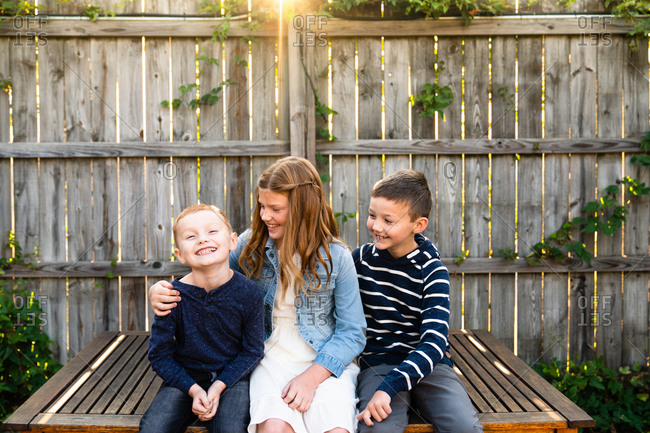 Three happy siblings sitting on wooden bench together