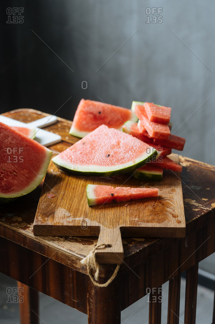 Watermelon being sliced on wooden cutting board