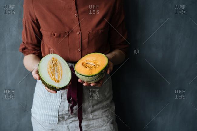 Woman holding two melon halves
