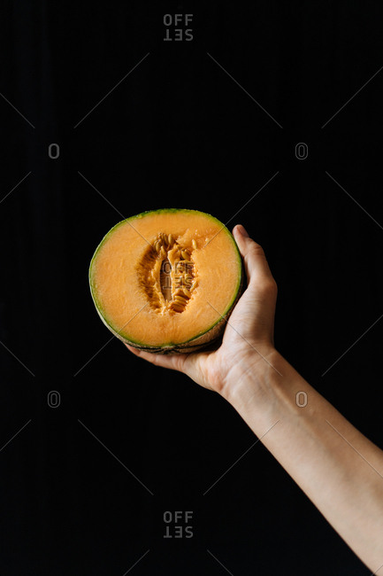 Hand holding a sliced melon in front of dark background