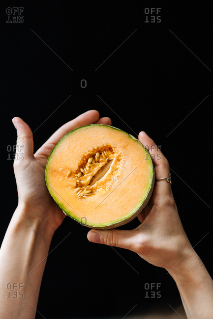 Hands holding a sliced melon in front of dark background