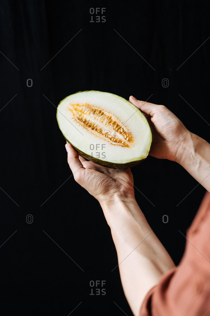 Hands holding a cut melon against a dark background