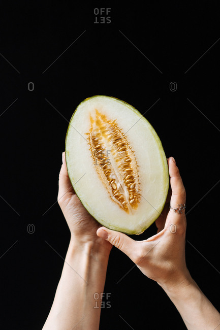 Woman holding a cut melon against a dark background