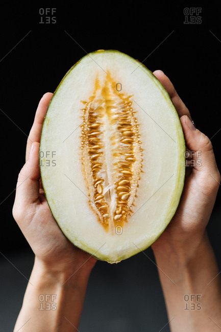Close up of hands holding a cut melon against a dark background