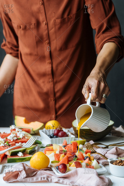 Female pouring sauce over fruit salad