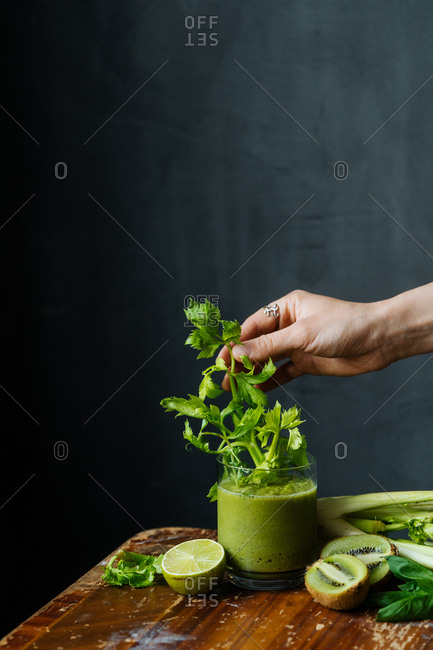 Woman putting celery into a green smoothie on a rustic table