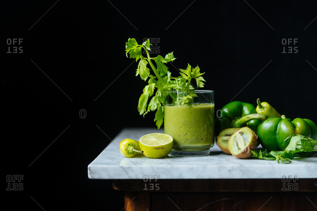 Close up of a healthy green smoothie with fruit and veggies on marble