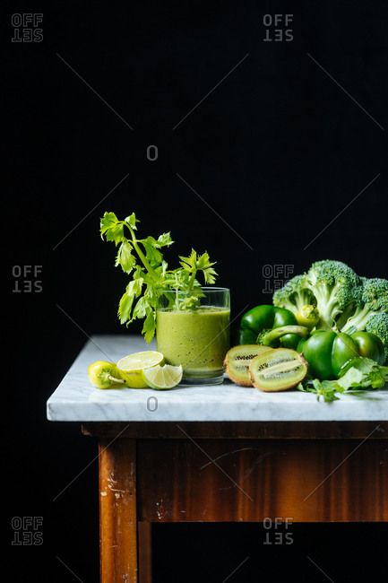 Healthy green smoothie with fruit and veggies on marble