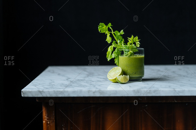 Healthy green smoothie with limes on marble table