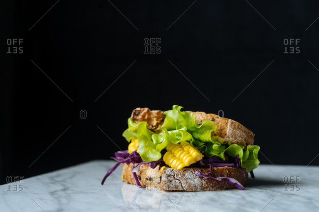 Sandwich on slate with lettuce, corn and red cabbage