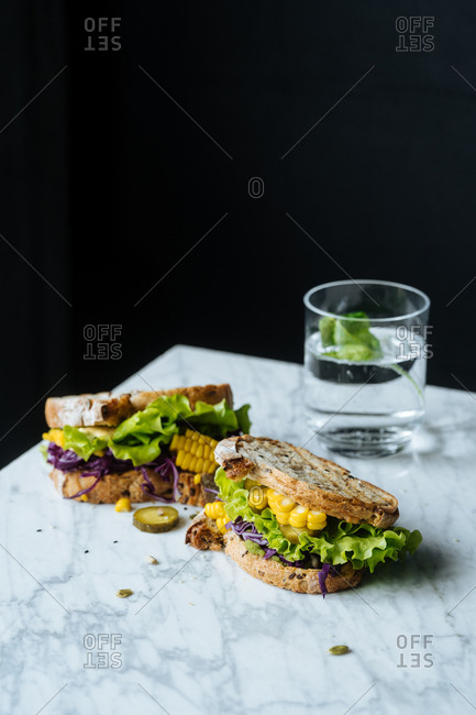 Two sandwiches on marble with lettuce, corn and red cabbage served with drink