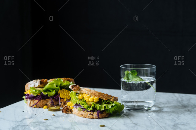 Sandwich on marble with lettuce, corn and red cabbage served with drink